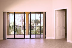 View of balcony. From inside house showing sliding glass doors and open door with tiled floor Royalty Free Stock Photos