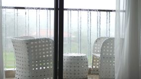 View of the balcony with table and chairs in the pouring rain with windy. slow motion. 3840x2160 stock footage