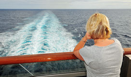 View from the Balcony of the Wake. A single woman watches the wake of a cruise ship from a back balcony Stock Image