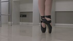View of a ballerina standing en pointe on the tips of her toes in a pair of ballet shoes.  stock video footage
