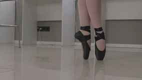 View of a ballerina standing en pointe on the tips of her toes in a pair of ballet shoes.  stock footage