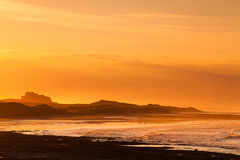 View of the  Bamburgh castle in a spectacular sunset Stock Photos