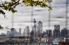 Blurred Bangkok cityscapes, bamboo blind, tree. View of Bangkok cityscapes with a tree on foreground through a bamboo blind on a bright sky day. Blurred stock photos