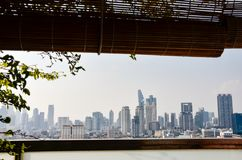 Blurred Bangkok cityscapes, bamboo blind, focused tree. View of Bangkok cityscapes with a tree from a terrace of a condominium in downtown with a bambooblind on stock photo