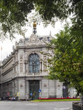 View of The Bank of Spain between trees and traffic Royalty Free Stock Photo