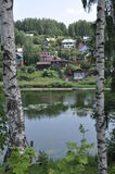 The view from the banks of the river to the mountain in small village houses through Russian white birch . Stock Photography