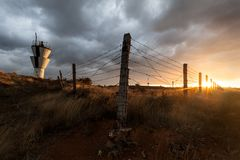 View through barbed wire fence on sunset stock photos