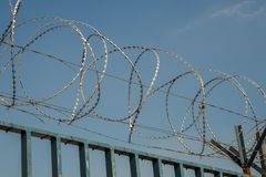 Barbed wire stretches along the blue painted metal wall. View of Barbed wire stretches along the blue painted metal wall stock image