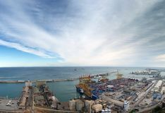 View of barcelona docks and harbour with shipping containers being loaded, warehouses grain silos and railway lines. With surrounding city industrial area and Royalty Free Stock Photo