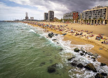A view of Barceloneta Beach. BARCELONA, SPAIN - JULY 15: Barcelona beachfront, considered between 10 best urban beaches of the world, crowded of people on Royalty Free Stock Image