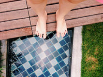 View of bare feet at canal side in the garden. Top view of bare feet at canal side in the garden Royalty Free Stock Image