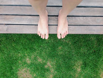 View of bare feet on green grass in the garden. Top view of bare feet on green grass in the garden Royalty Free Stock Images