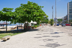 View of Barra da Tijuca beach with palms and mosaic of sidewalk Stock Image