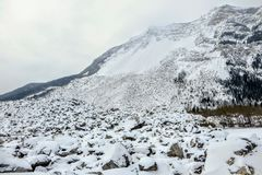 The view from a base of a mountain where a huge rock slide took place. Huge boulders line the mountain covered in snow. royalty free stock photography