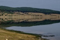 View of Batak dam reservoir, coastal autumn glade, forest with reflection and hills at Rhodope mountains royalty free stock photography