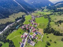 View of bavarian alpine village with a valley and mountains, shot from drone, Bayern, Bavaria, Germany, sunny summer day Royalty Free Stock Photo
