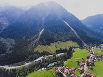 View of bavarian alpine village with a valley and mountains, shot from drone, Bayern, Bavaria, Germany, sunny summer day Stock Photos