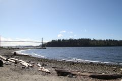 A view of a bay from a beach with driftwood sand and rock. In the foreground and the Lion`s Gate bridge and Stanley Park in the background on a sunny day with royalty free stock photography