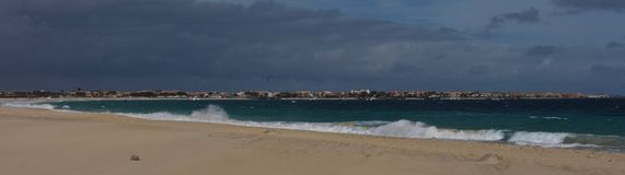 Deserted beach at Cape Verde with view of Santa Maria. View of bay in Cape Verde overlooking the town of Santa Maria, with deserted beach and surf of bluegreen royalty free stock images
