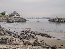 View of a bay with its beach with rocks with a terrace on rocks a bridge with the sea in the background stock photo
