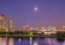 View of the bay of Odaiba with daiba park and the beach in the d. Istance in the full moon illuminated purple night sky royalty free stock photography