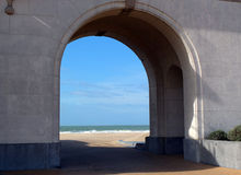 View of the beach through the arcade. View of the beach of northern -sea through the arcade  of Palais des Thermes in Ostend, Belgium, Europe Royalty Free Stock Photos