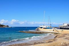 Beach and harbour, Marsalforn, Gozo. View of the beach with boats and yachts in the harbour to the rear, Marsalforn, Gozo, Malta, Europe Stock Image
