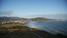 View on beach break waves on surf beach. Beautiful view from mountain on small hidden town in front of long empty surf beach next to ocean with breaking waves in stock video