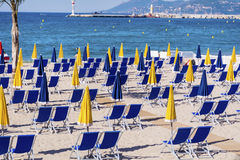 View of the beach at Cannes with chairs and parasols on white sandy beach Stock Photo