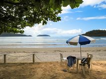 View of the beach with chair and umbrella in the foreground. View of the beach, with chair and umbrella the shade of tree in the foreground, with coast and Royalty Free Stock Photo