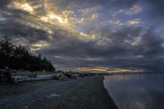 Sunset Sequim Washington Beach. View of beach and driftwood at dusk with sunset backgroung Royalty Free Stock Photo