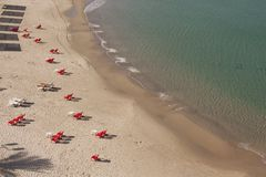 View of the beach with empty chairs on top. Empty beach with groups of red plastic chairs and white sunbeds prepared for vacationers Shot was taken from the top royalty free stock images