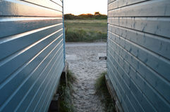 View between beach huts onto marshlands with summer sun setting Stock Photo