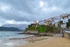 View from the beach of Lastres, Asturias, Spain, of the town, in. A cloudy day. Small town in front of the sea over a cliff stock images