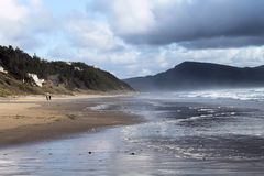 View From the Beach. Looking down the Pacific coastline as storm clouds gather Stock Photo