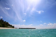 View of the beach with palm trees and azure water. sunny tropical day.agull sky.  Stock Photos