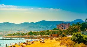 View of the beach of Palma de Mallorca. With people lying on sand and the gorgeous cathedral building visible in background. Palma-de-Mallorca, Balearic islands Stock Photos