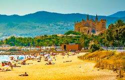 View of the beach of Palma de Mallorca. With people lying on sand and the gorgeous cathedral building visible in background. Palma-de-Mallorca, Balearic islands Royalty Free Stock Photo