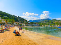 View of the beach of Port de Soller with people lying on sand, Soller, Balearic islands, Spain. Royalty Free Stock Photos