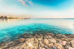 View of the beach with some people swimming in the turquoise sea. Protaros, Cyprus royalty free stock photo