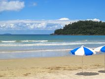 View of beach with parasol and island in the background. View of beach on sunny day with umbrella and island and clouds in the background Stock Photography