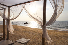 View of a beach in sunset through the curtains of a beach bed Royalty Free Stock Photo