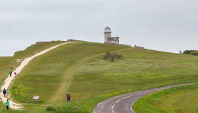 View of Beachy Head with walkers and the Belle Toute Lighthouse Stock Photo
