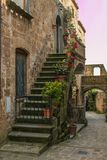 View of beautiful alley with flowers in the historic center of Civita di Bagnoregio village at sunset, Lazio Stock Image