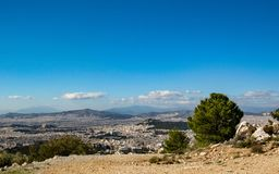 Cityscape of Athens city from Mount Hymettus with white buildings architecture, mountain, trees and blue sky stock image