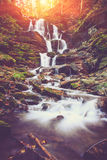View of a beautiful autumn waterfall in mountains. Royalty Free Stock Photography