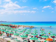 View of the beautiful beach and the sea in Alghero. Beach-goers renting on sun loungers. stock images