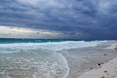 View of a beautiful beach with white sand in Cuba. It´s a cloudy day and there are some waves in the ocean Stock Photos