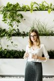 Beautiful caucasian businesswoman standing at her office by gree. View at beautiful caucasian businesswoman standing at her office by green plants and drinking Royalty Free Stock Photos