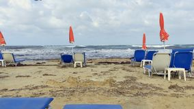 Deck chairs with umbrellas on the beach. View of beautiful emerald sea with blue cloudy sky. Waves covers the beach. Silence and nobody around. Bewitching nature stock footage
